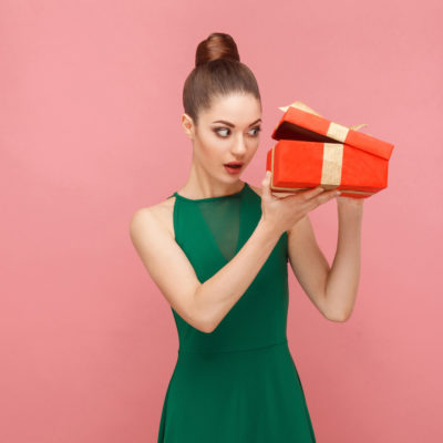 Woman unboxing red gift box looking inside.