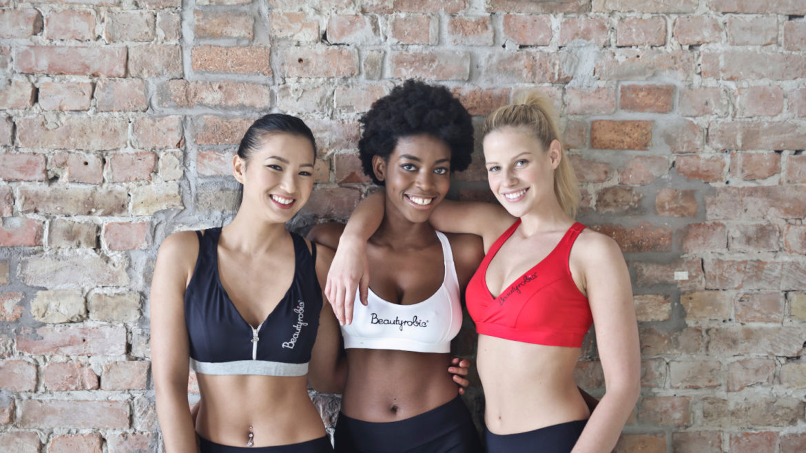 Three diverse women wearing sports bras and leggings while standing in front of a brick wall.
