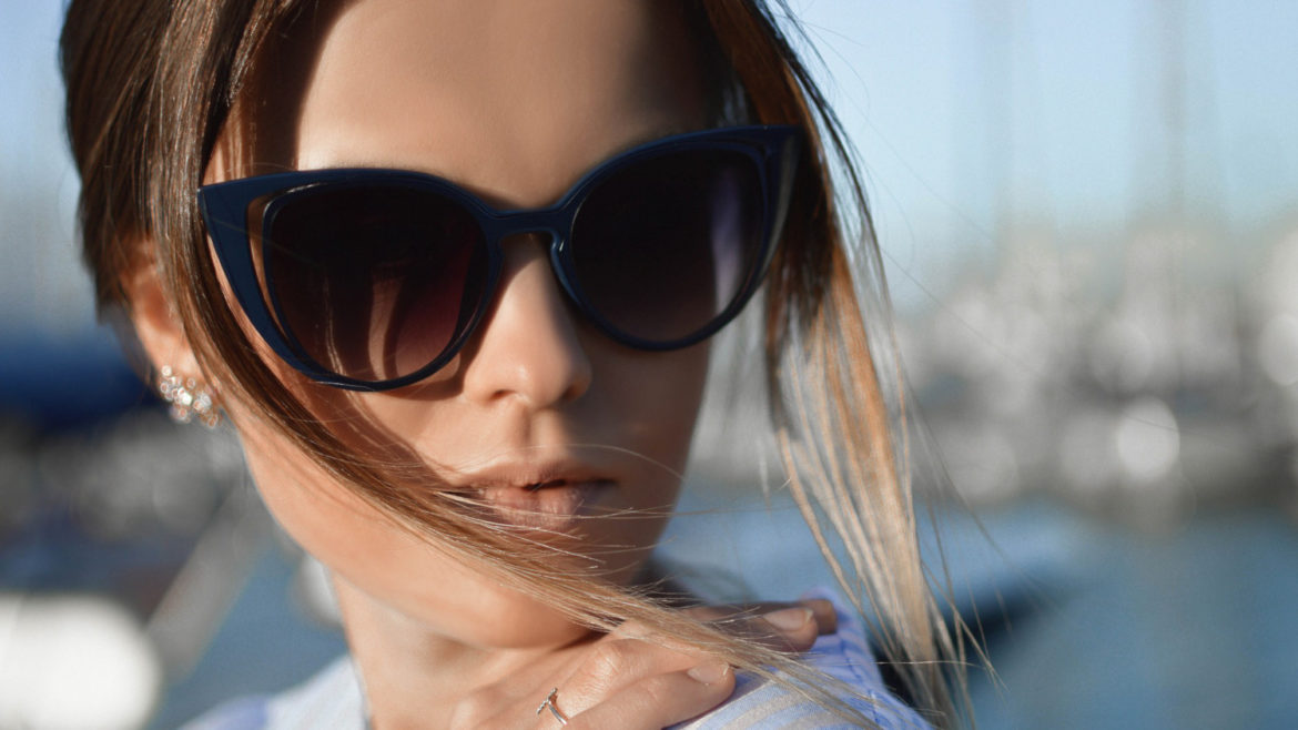 Close-up portrait of a female model with smooth skin wearing posh sunglasses.