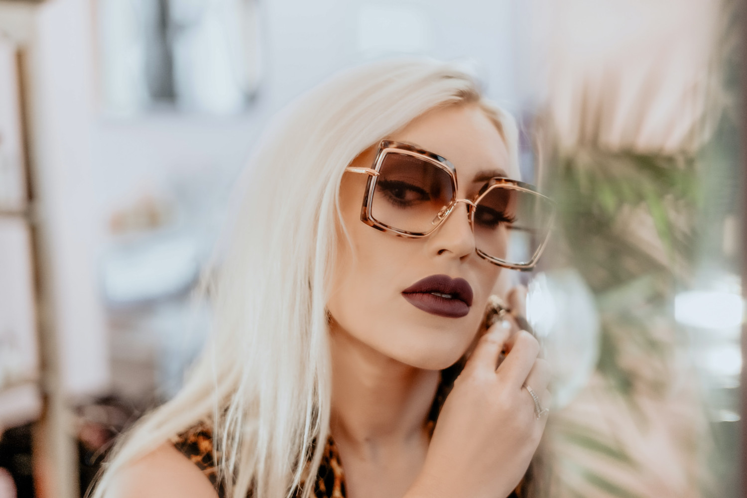 Woman wearing dark brown lipstick and oversized tortoise shell sunglasses.
