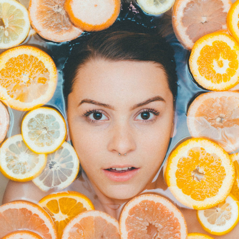 Woman's face surrounded by sliced lemons floating in water.