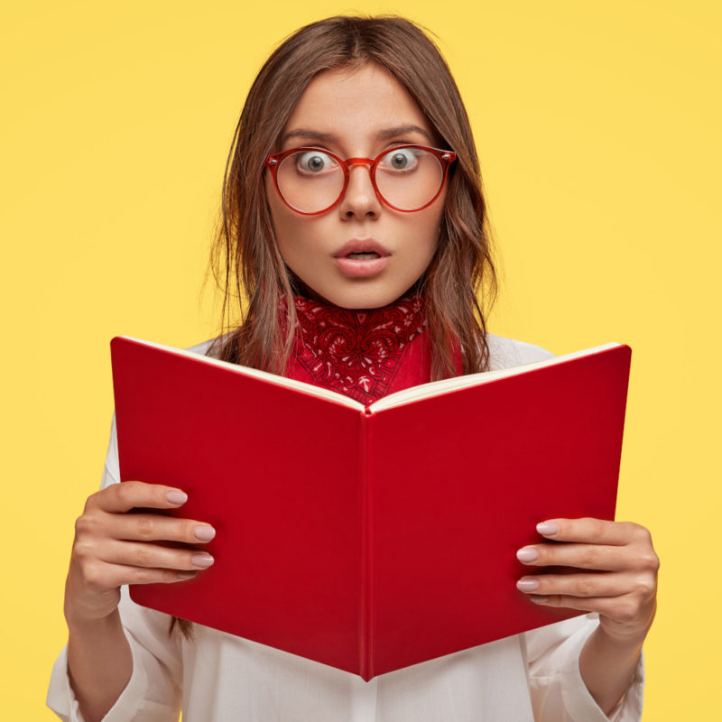 Lovely woman wearing glasses holding a book looking concerned about the information she is reading in front of an isolated yellow background.