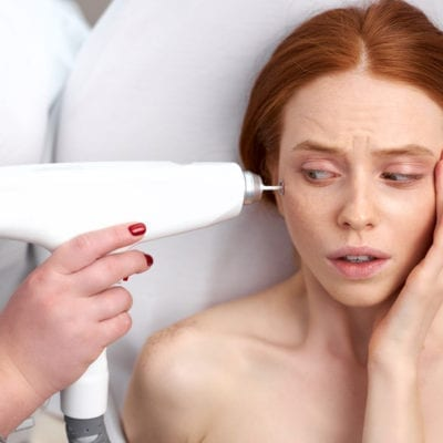Red haired woman scared by laser treatment on face, looking at equipment.